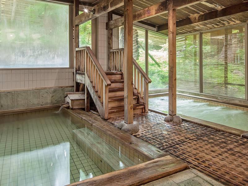 【あじゃらの湯】ほのかに木の香り漂う、広くゆったりした開放的な大浴場です。周辺を緑で囲まれた開放感とともに温かなお湯でのんびりとお寛ぎください。