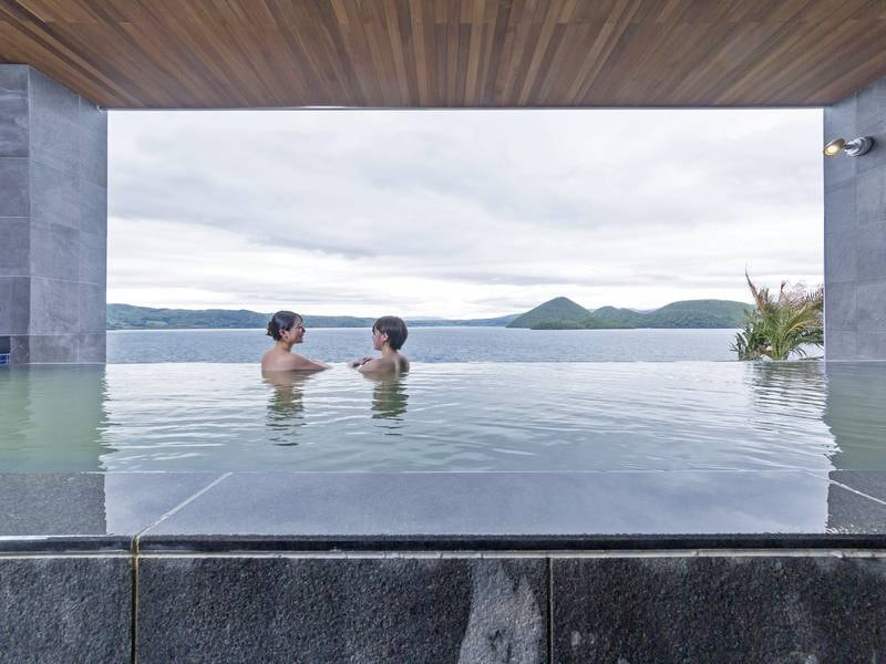 【8階・星の湯】浴槽に浸かると洞爺湖面と一体に感じる設計。すぐ横に寝湯や、壺湯あり