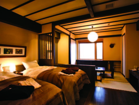 ベッドと畳空間が、民芸調の木調でまとめられた和洋室/例
