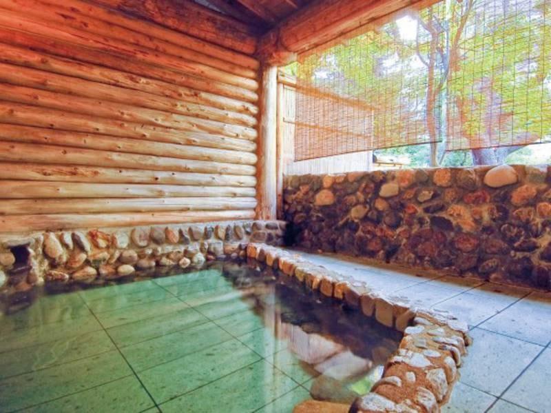 【露天風呂(昼)】露天風呂からは四季折々の表情豊かな庭園が眺められ、心も体も癒される。