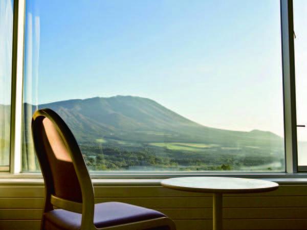 【岩手山側客室・眺望/例】窓から雄大な景色を一望する