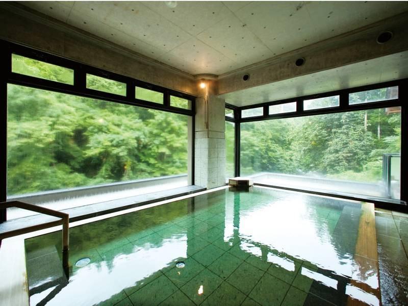 【大浴場/山水の湯】高い天井と大きなガラス窓が印象的な大浴場
