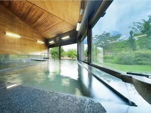 【大浴場】窓越しの緑に癒される、薬石「光明石」を使用したお風呂