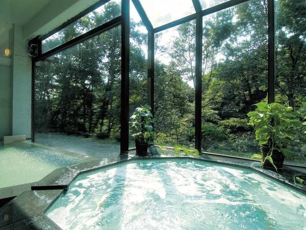 【大浴場】ジャグジーバスのバブルと窓の外に広がる木々にリラックス