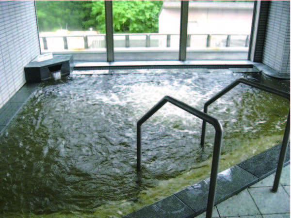 【大浴場】茶褐色の源泉かけ流しの湯が注ぐ