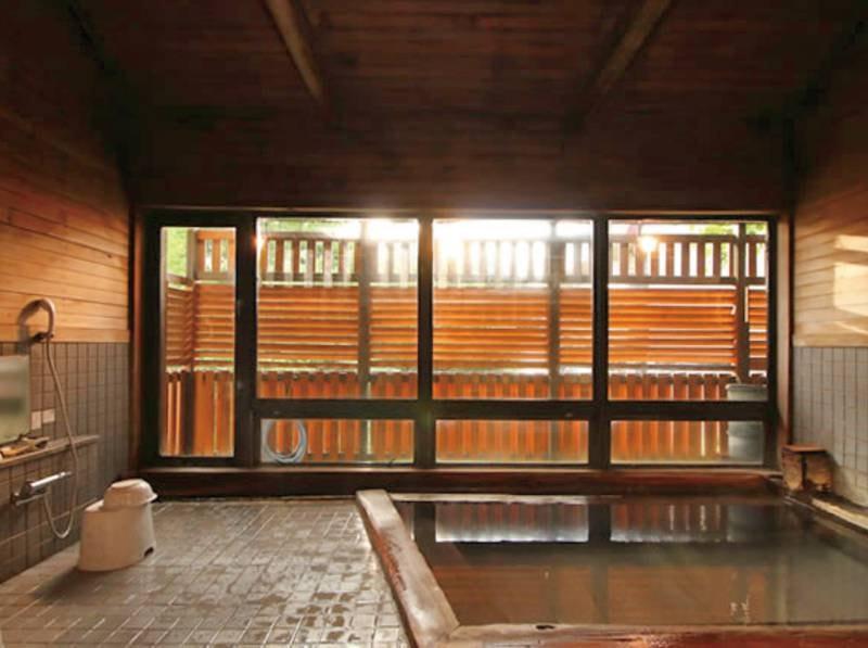 【大浴場】檜の湯船と硫黄の香りで、ゆったりとお湯に浸かる