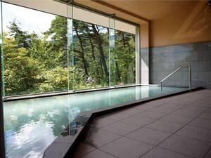 【大浴場/山の湯】大きな浴槽とガラス張りの浴場で開放感が魅力