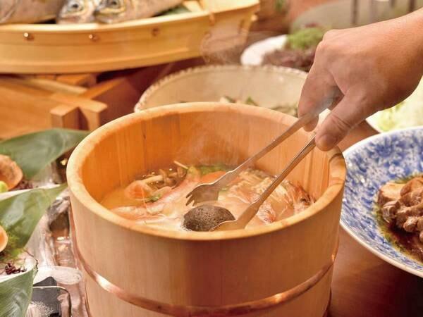 【石焼き桶鍋/例】アツアツの焼き石を投入して沸騰させる宿の新名物料理