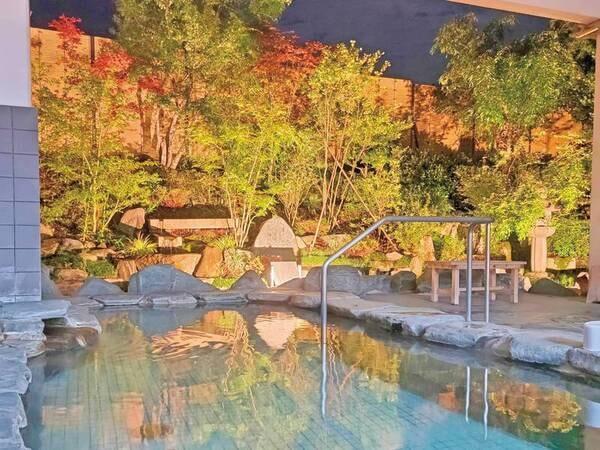 【和風露天風呂(夜)】岩肌を模したシックな浴場。自慢の自家源泉が滾々と注がれる。