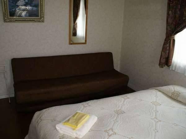 お部屋のソファはご利用人数によってエキストラベッドへ変更可能