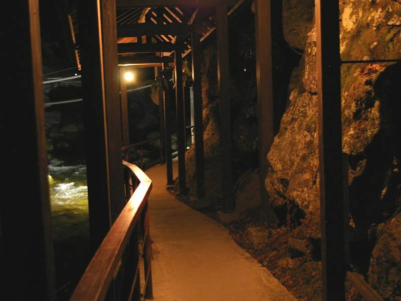 【渡り廊下】自噴巌風呂へはこちらから…。裸電球の明かりが優しく川沿いの廊下を燈します。