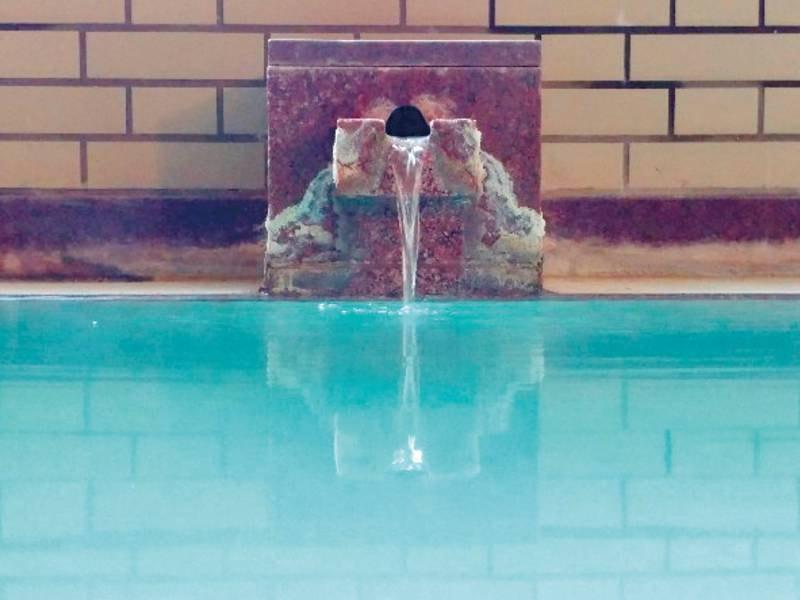 【大浴場】岳の湯は青みがかっていて、湯舟の底には湯の花がまっています