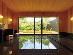 【大浴場/湯処「風花」】黒の浴槽と檜のコントラストが美しい空間