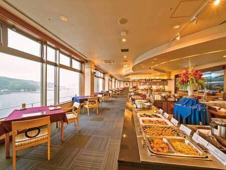【食事会場/例】海を望む開放的なレストランで食事を楽しめる。座席の間隔への配慮など、ホテルの心配りが光る。